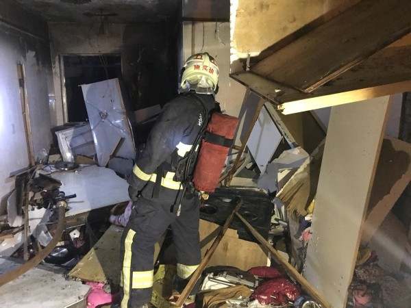 Firefighter inside damaged home.