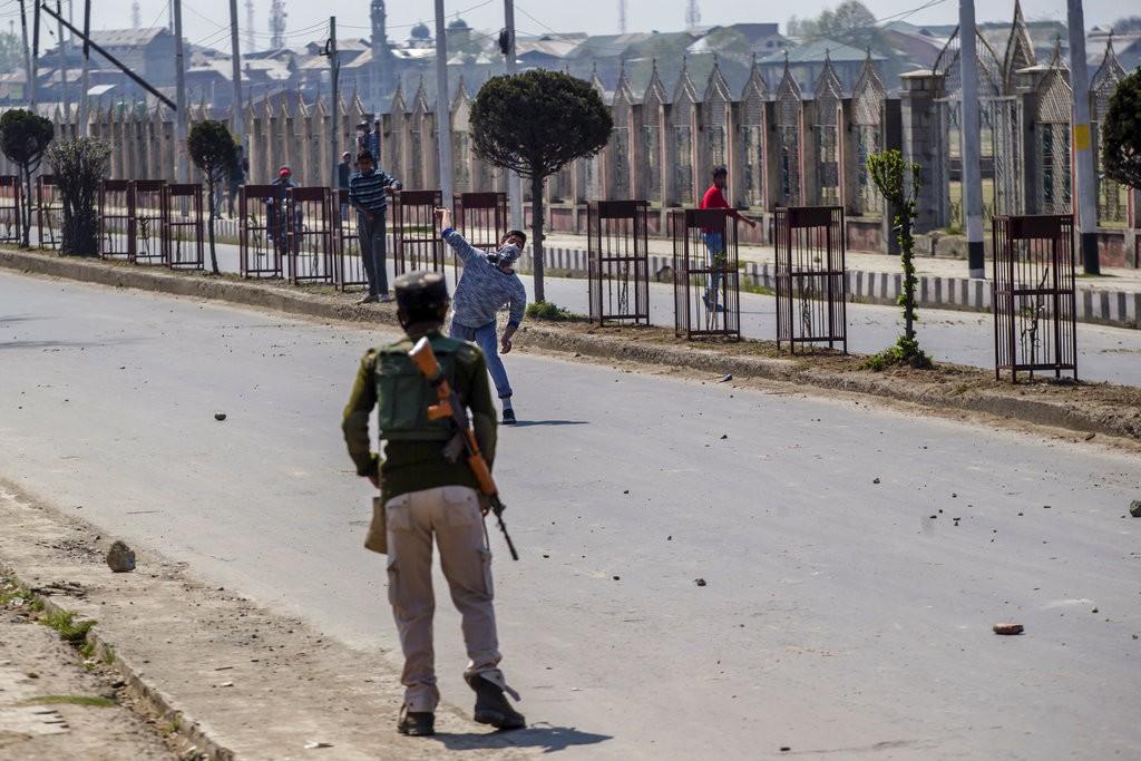 一位抗議民衆對印度軍方投擲石塊(圖片來源:美聯社)