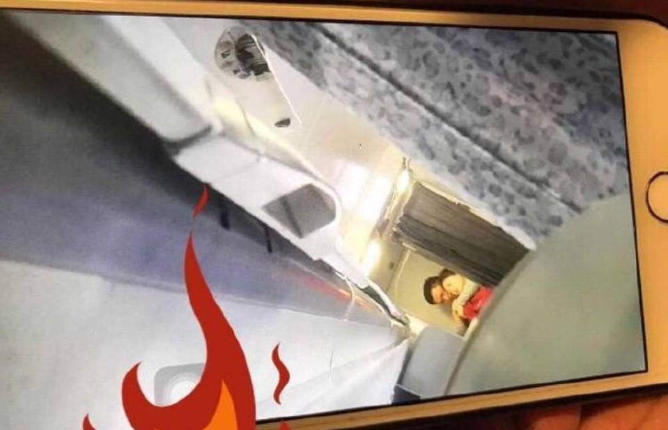 中國微博流傳一張旅客用手機拍下的照片,可以看到一名女性空服員遭到挾持。翻攝自微博