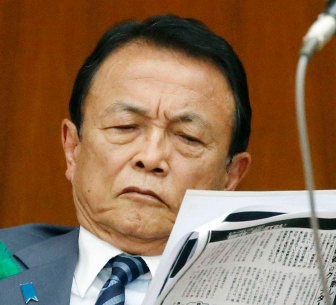 日本財務大臣麻生,閲讀報導財務省事務次官性騷女記者的雜誌文章(美聯社)