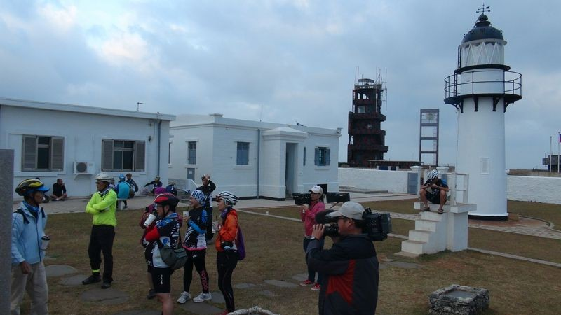 Tourists at the Xiyu Lighthouse in Penghu with the military radar installation in the background.