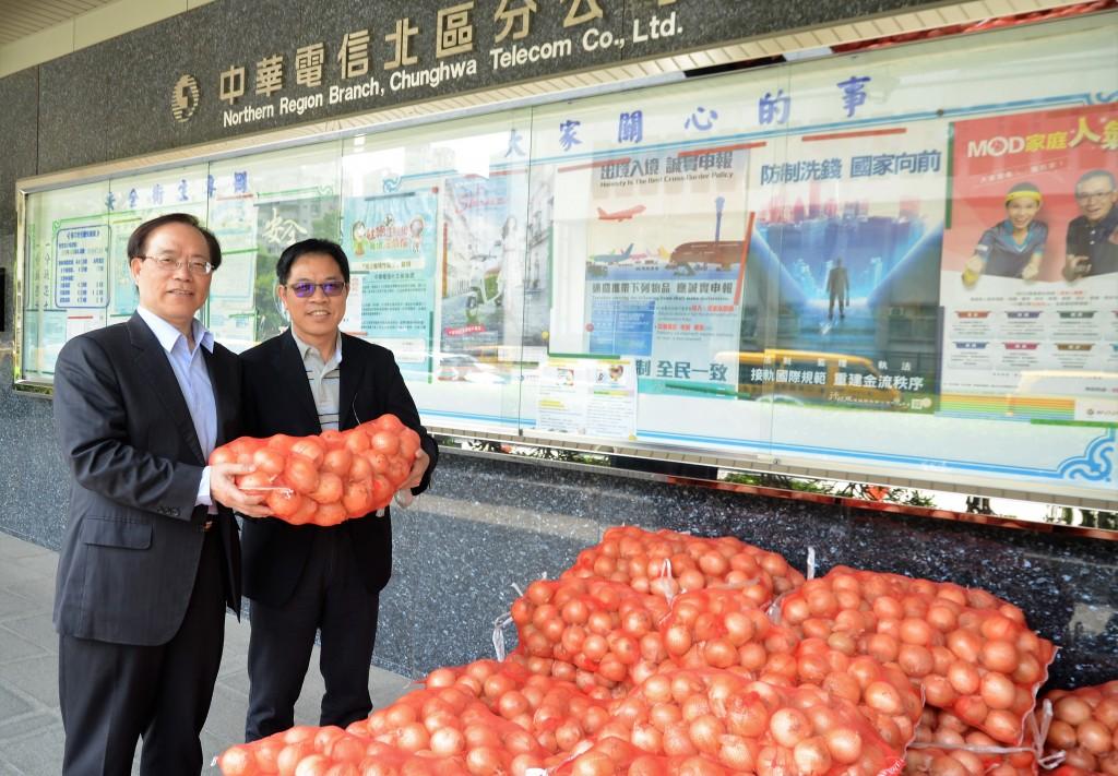總經理謝繼茂(左)一早把剛從南部運上來的洋蔥交給北區分公司副總張義豐(右)分送各營運處。(照片由中華電信提供)