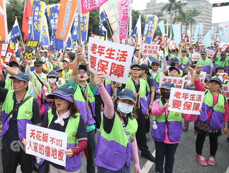 2018五一行動聯盟1日發起「五一勞工大遊行」,從凱道集結出發前往立法院,遊行民眾高舉標語表達立場。中央社