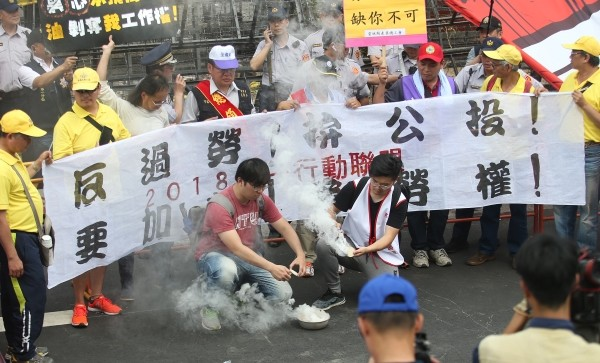 Workers release smoke in protest.