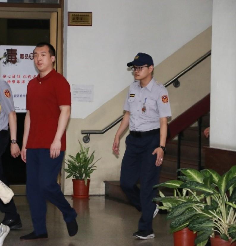 中國籍男子周泓旭(紅衣者),8日獲高院合議庭當庭釋放。中央社