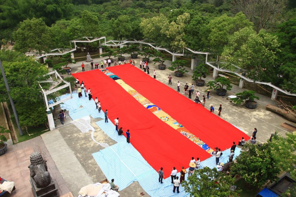 台南市左鎮區台灣噶瑪噶居寺將於19日舉辦曬大佛展佛法會,向印度訂製的大尺寸大佛唐卡在廣場鋪平,相當壯觀。