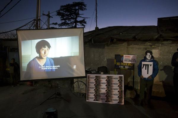 一名流放的西藏人士,站在播放著紐時紀錄片的螢幕旁,聲援扎西文色(照片來源:美聯社)