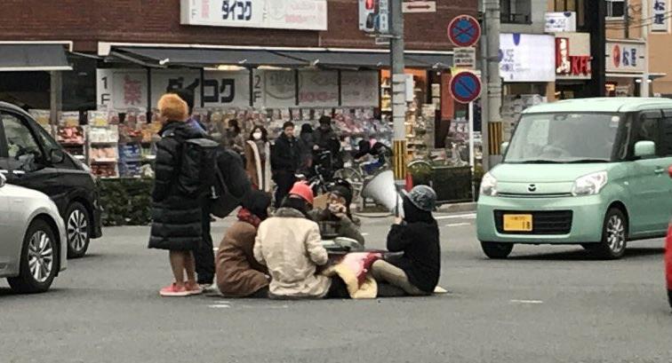 京都大學學生坐在馬路上取暖(翻攝自推特)