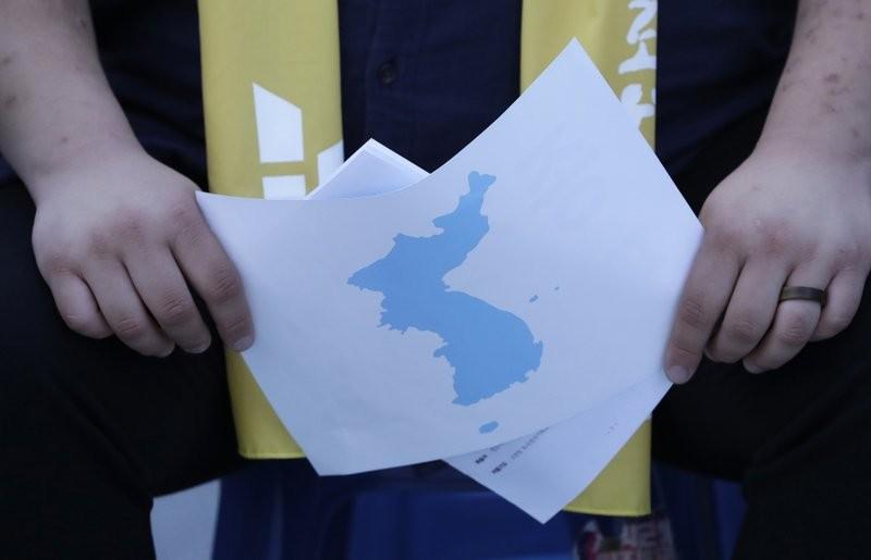 南韓民眾手握朝鮮半島地圖 (美聯社)