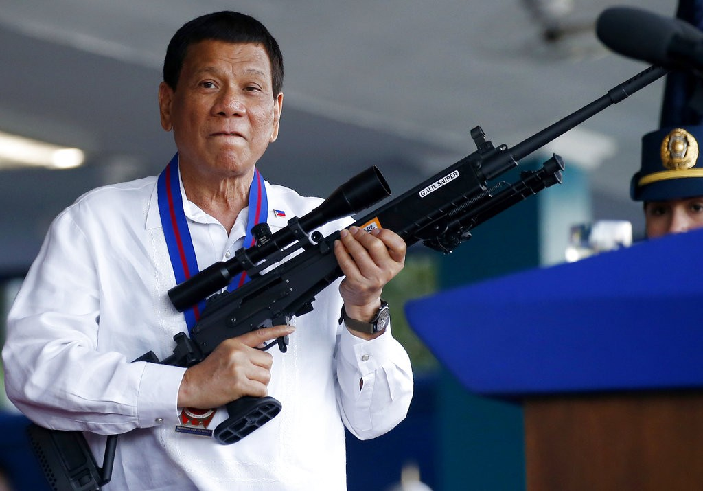President Duterte holding a firearm during an event in Quezon City, April 19, 2018