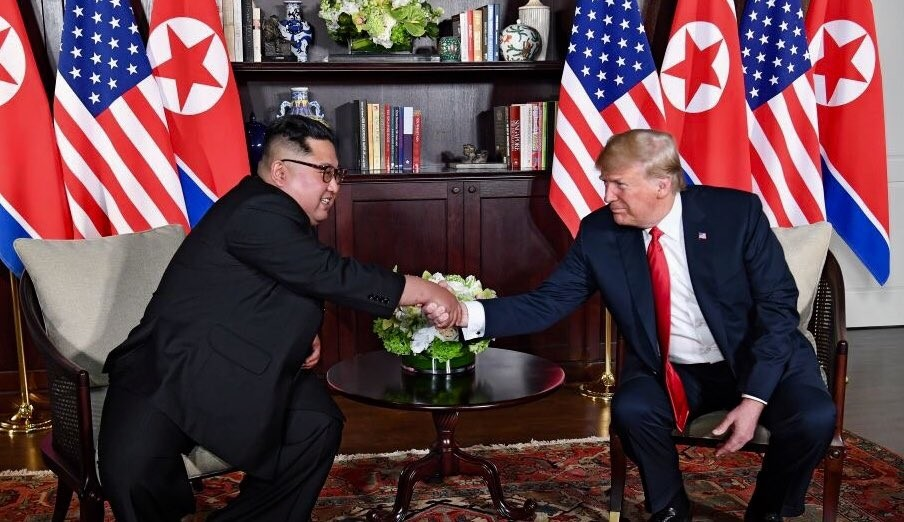 Kim (left) shakes hands with Trump (right).