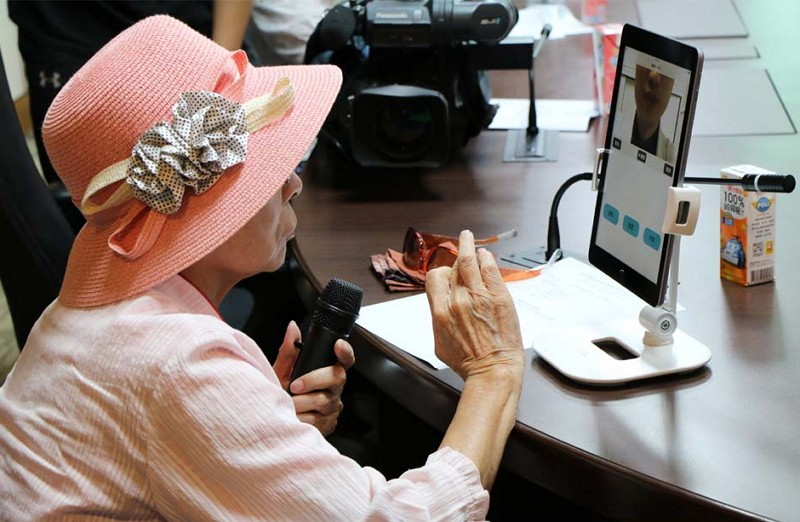 An old lady shows no difficulty in using the hearing aid app (Photo by Taipei Veterans General Hospital)