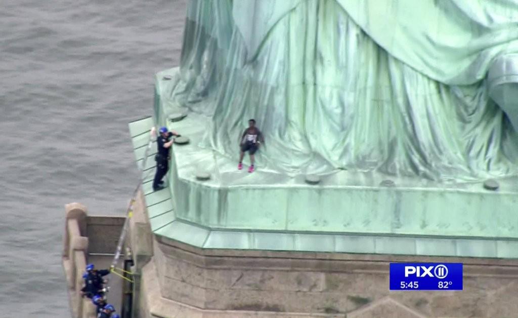 民衆爬上自由女神像抗議。警方進行勸説(美聯社提供)