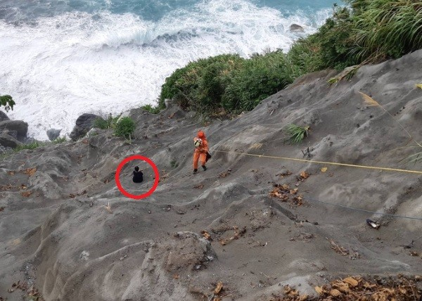 Woman being rescued from seaside slope.