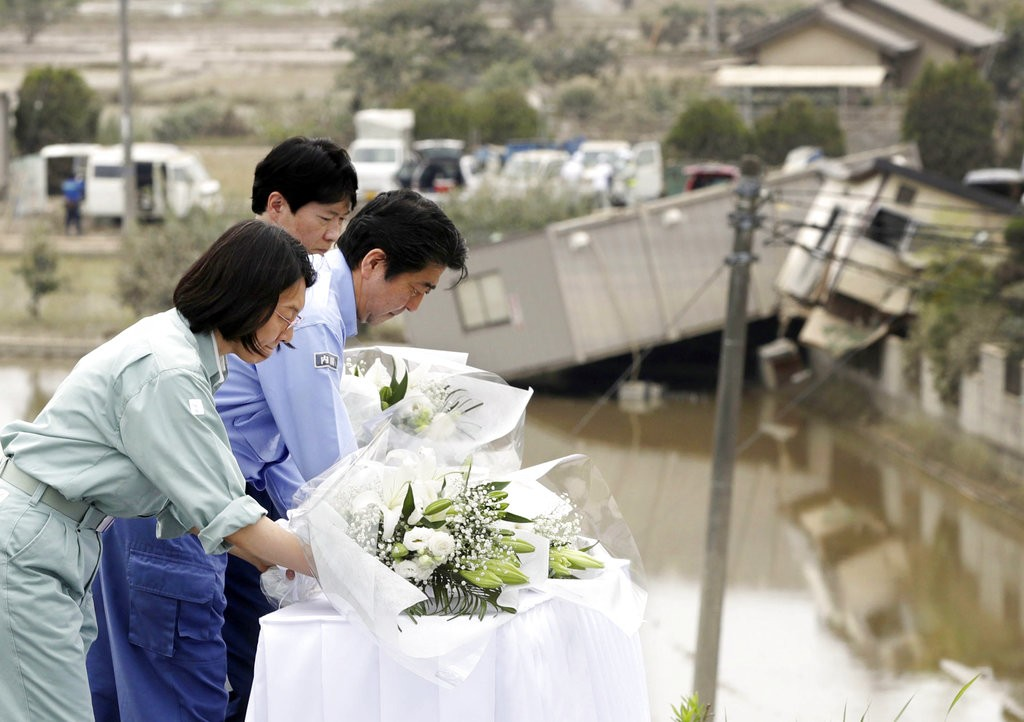 Abe offers flowers for the victims in Kurashiki, Okayama prefecture.