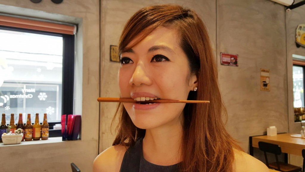 "Woman using chopstick to practice ""social smile."""