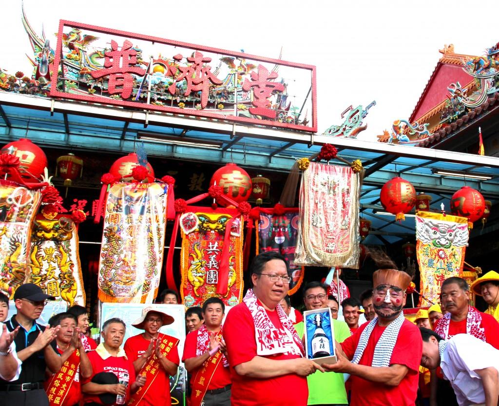 關公慶生熱鬧出巡,日本文化團體代表(右)與桃園市長鄭文燦(左)互贈禮物(照片拍攝:劉怡均)