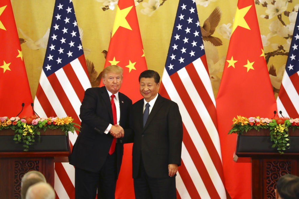 Trump and Xi shake hands in front of their respective national flags