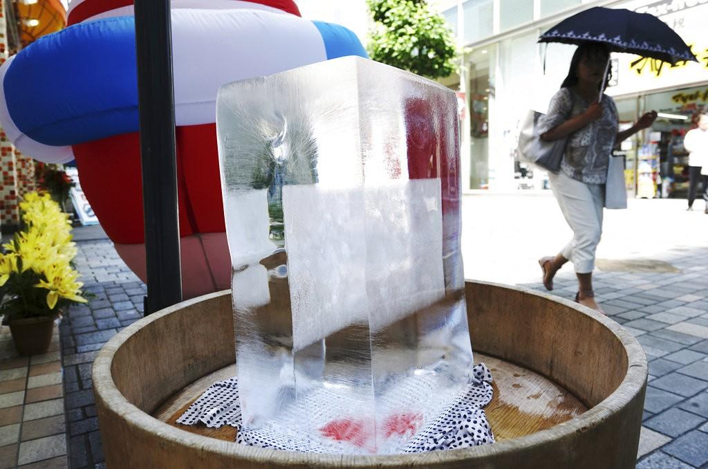 東京街頭用冰塊降熱(美聯社提供)