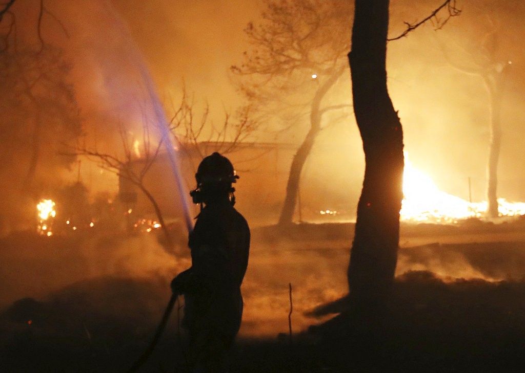 希臘森林大火,一名消防員正用強力水柱撲滅(圖片來源:美聯社)