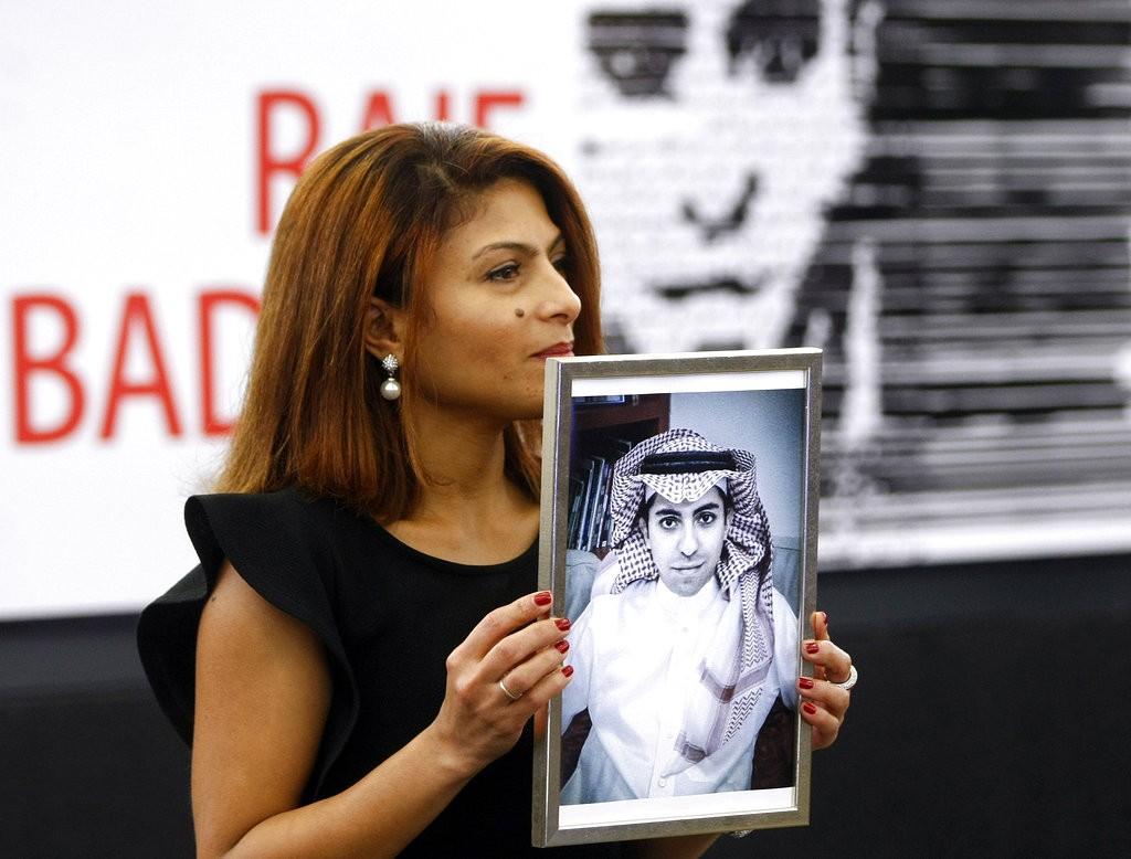 沙烏地阿拉伯人權鬥士妻子手持其丈夫頭像(美聯社)