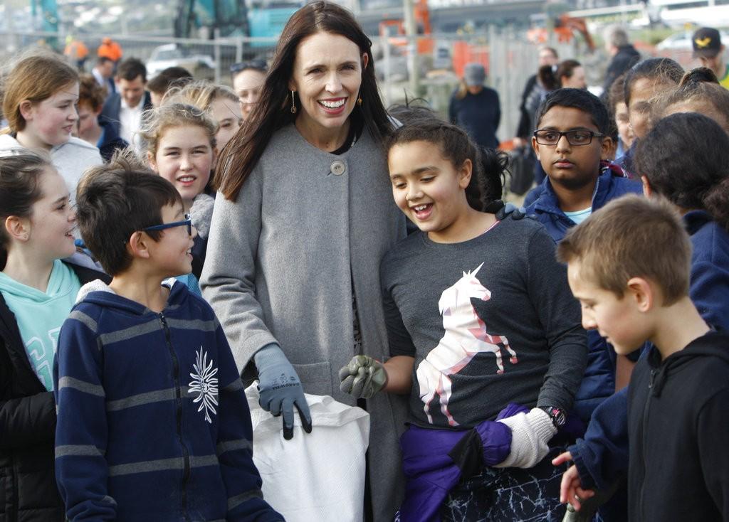 紐西蘭總理傑辛達·阿爾登(Jacinda Ardern)與小朋友在海邊清理塑膠廢物(美聯社)