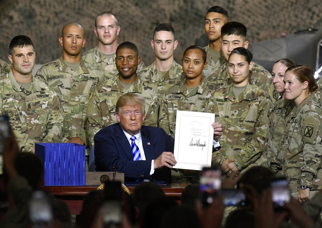 Trump holding up newly signed NDAA bill.