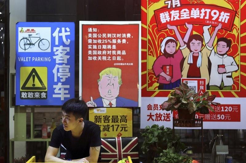 美中貿易戰,廣州餐廳外海報寫著,將對美國消費者收取25%服務費(美聯社)