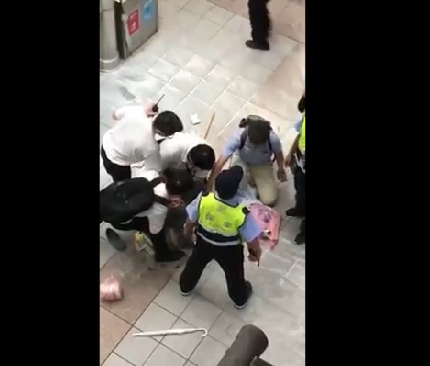 Police force woman with knife to the ground at Taipei Longshan Temple MRT station (image courtesy of Baoliao Gongshe)