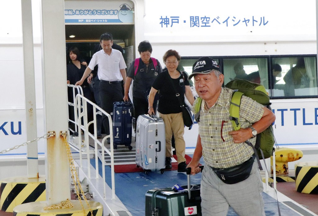 燕子颱風侵襲日本大阪關西機場,旅客搭乘接駁船赴神戶機場(共同社。美聯社提供)