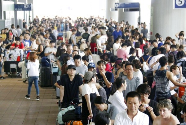 Passengers wait in line to board buses to evacuate Kansai Airport.
