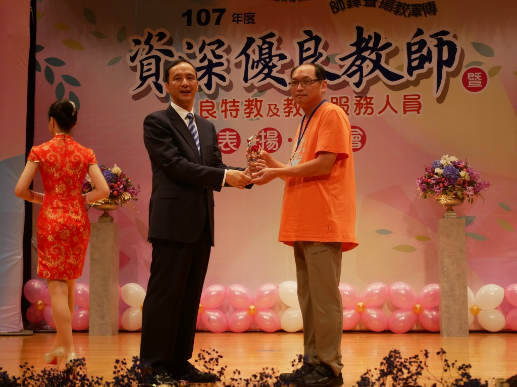 林老師的先生代表服務滿20年的林淑綾老師領獎 (新北市政府教育局提供)