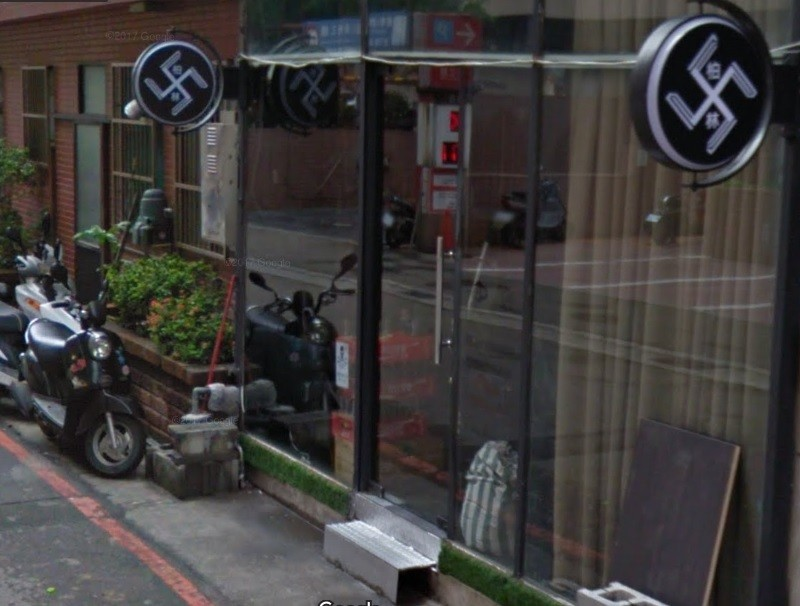 "Google Street View image of storefront, including two ""swastika' logos."