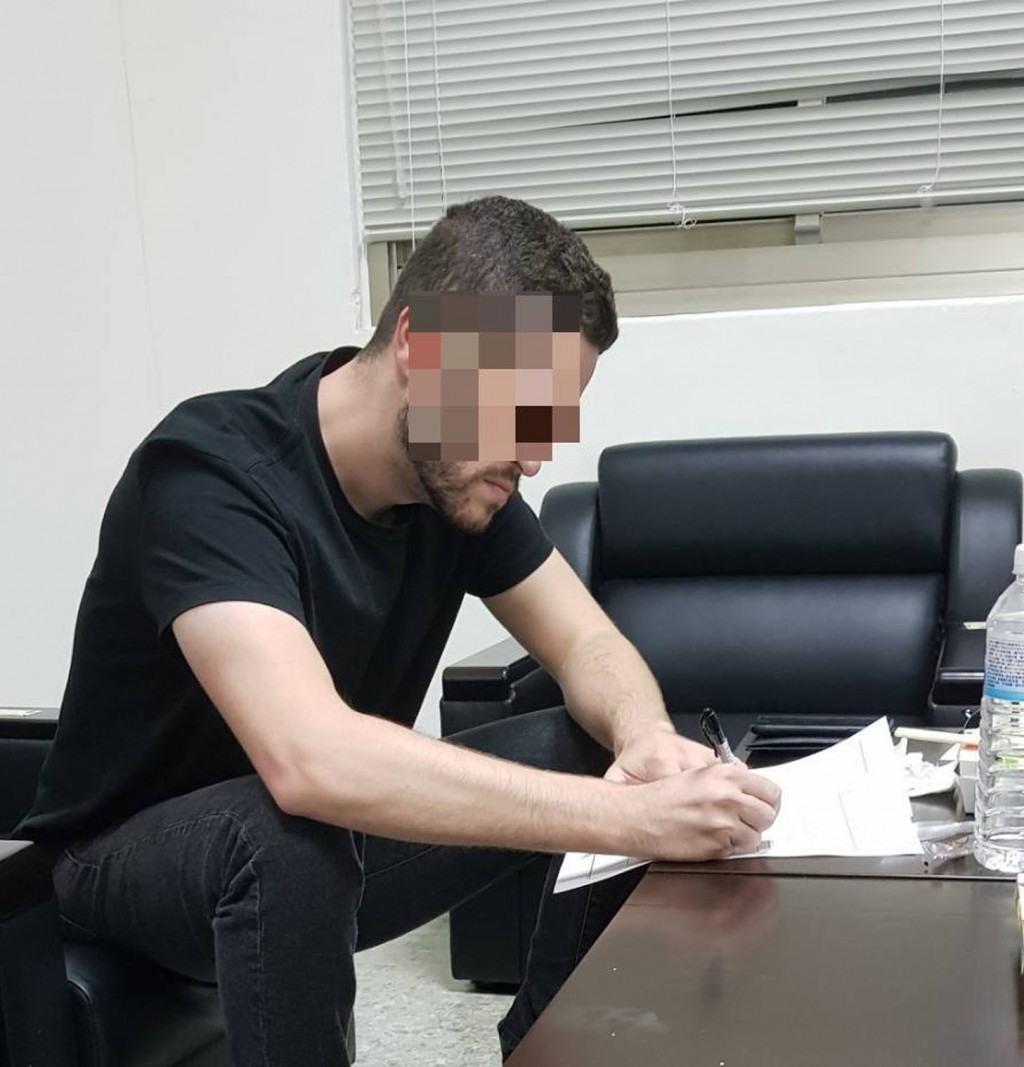 Cody Wilson signing a document at the NIA (photo courtesy of NIA)