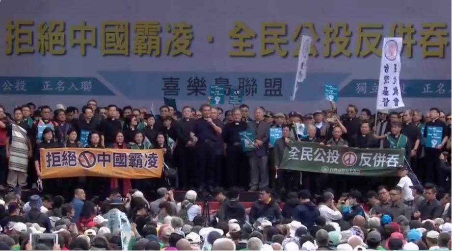 喜樂島聯盟發起的「反併吞正名公投」活動20日下午在台北市民進黨中央黨部前舉行,圖為長老教會牧師群在台上高歌,並為台灣人民祈禱。(圖片翻攝自