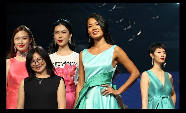 "Designer May Hsu (fwd left) with models showcasing ""Madam May"" brand designs"