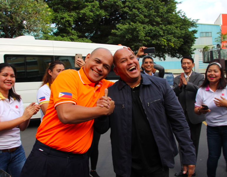 Philippines corrections chief Ronald dela Rosa (front right) meets a look-alike among Filipino staff at I-Mei in Taoyuan Friday.