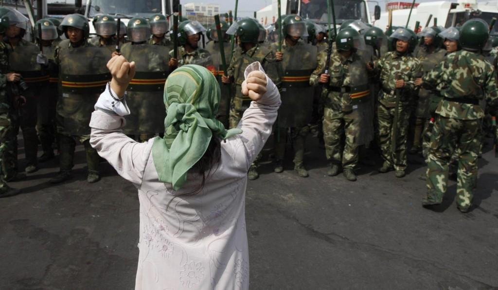 A Xinjiang woman facing a riot squad in 2017