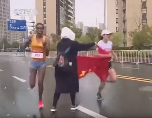 Volunteer trying to hand flag to runner. (Screenshot from DiaoZhaErTV2)