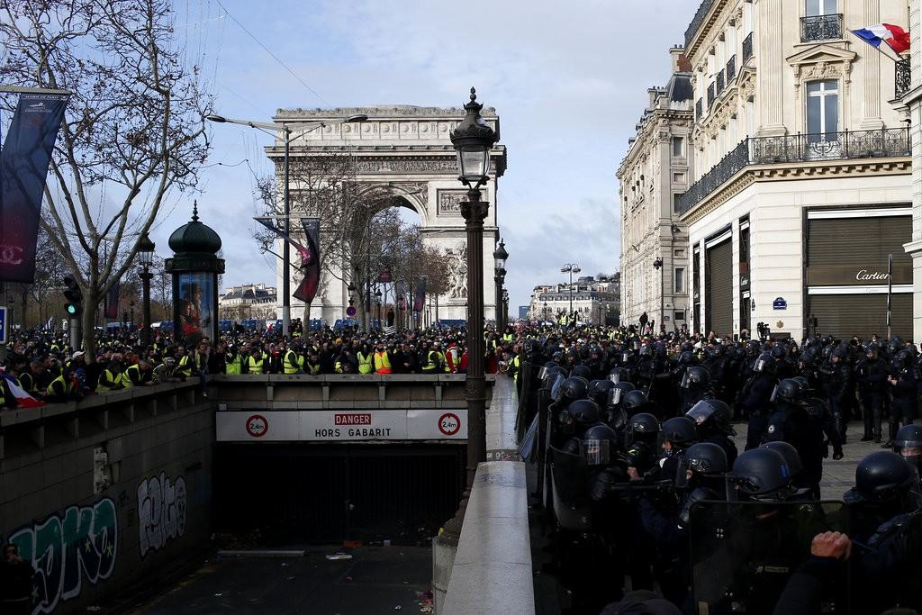 法國黃背心抗議群眾8日在香榭麗舍大道前聚集抗議。(圖片來源:美聯社)