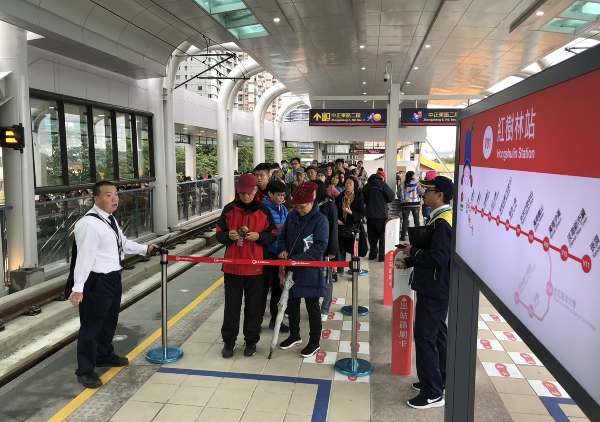 Crowds wait to board the Danhai Light Rail on the 1st day of test rides for the public