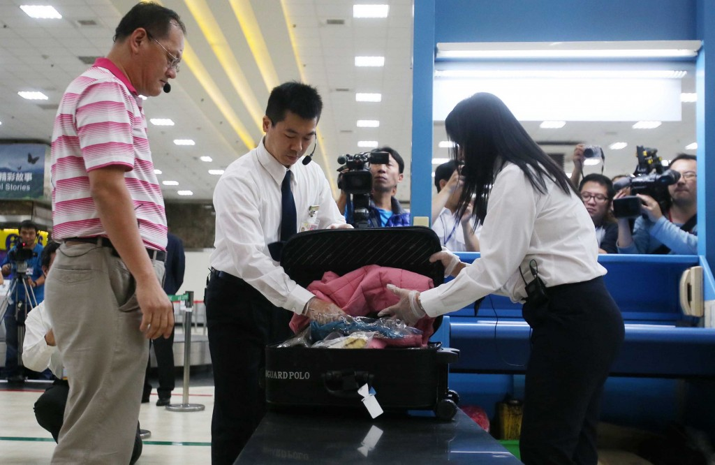Customs official inspects bag.