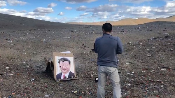 Kazakh man firing at Xi Jinping photo. (Still from YouTube video)