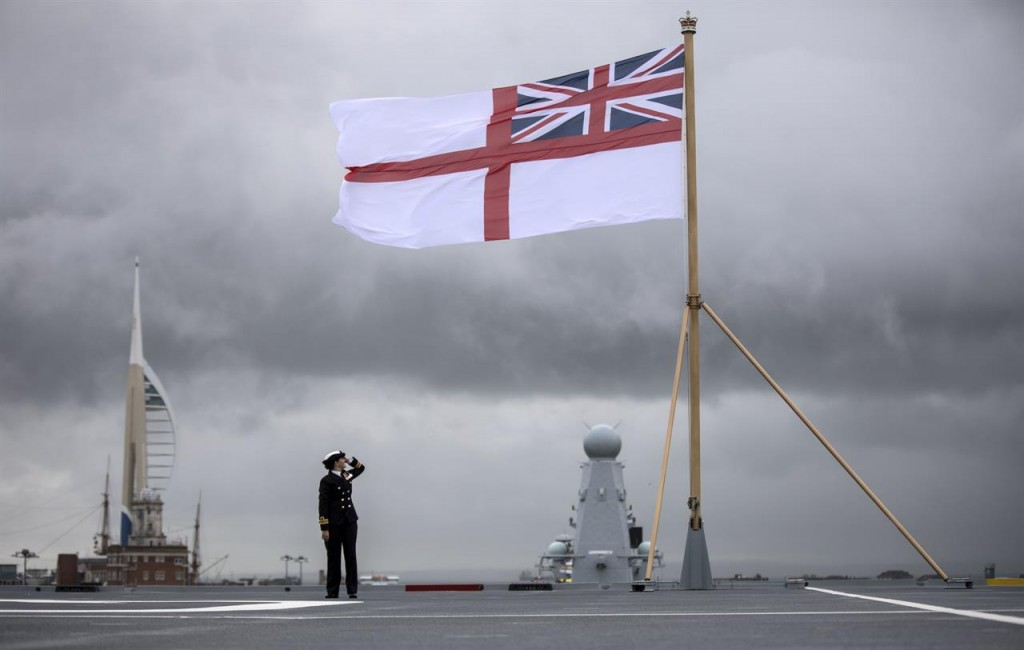 A sailor salutes the flag of the Royal Navy aboard the HMS Queen Elizabeth