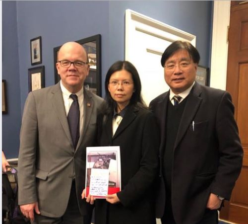 Lee Ching-yu (center) holding the message from Congressman Jim McGovern (left), with human rights official Yang Sen-hong (screenshot from Facebook pag...