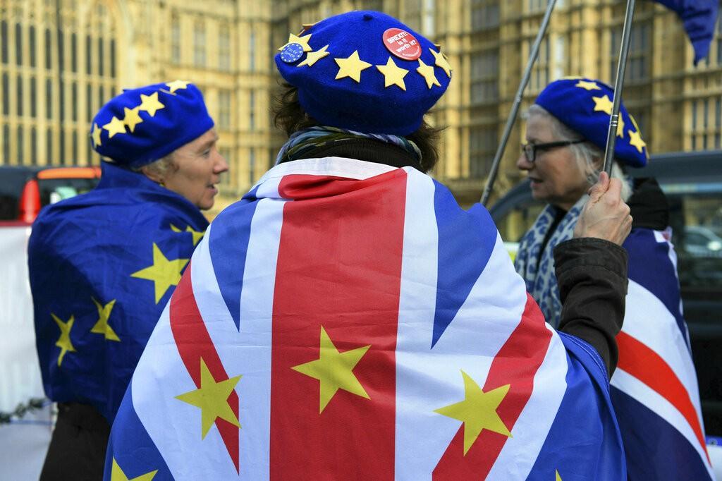 英國反脫歐人士2019年2月13日聚集在倫敦國會大廈前搖旗表達反對脫歐立場。(圖片來源:美聯社)
