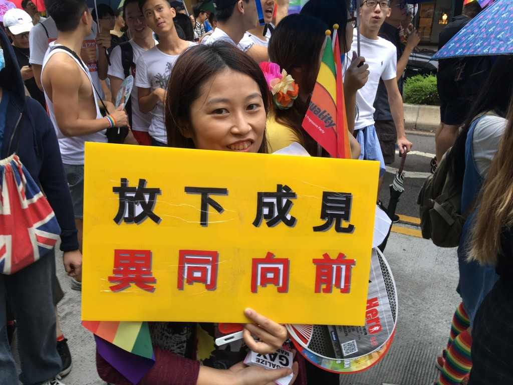 """The photo shows a gay parade participant in 2016 holding a sign reading """"lay down prejudices, move forward together."""""""