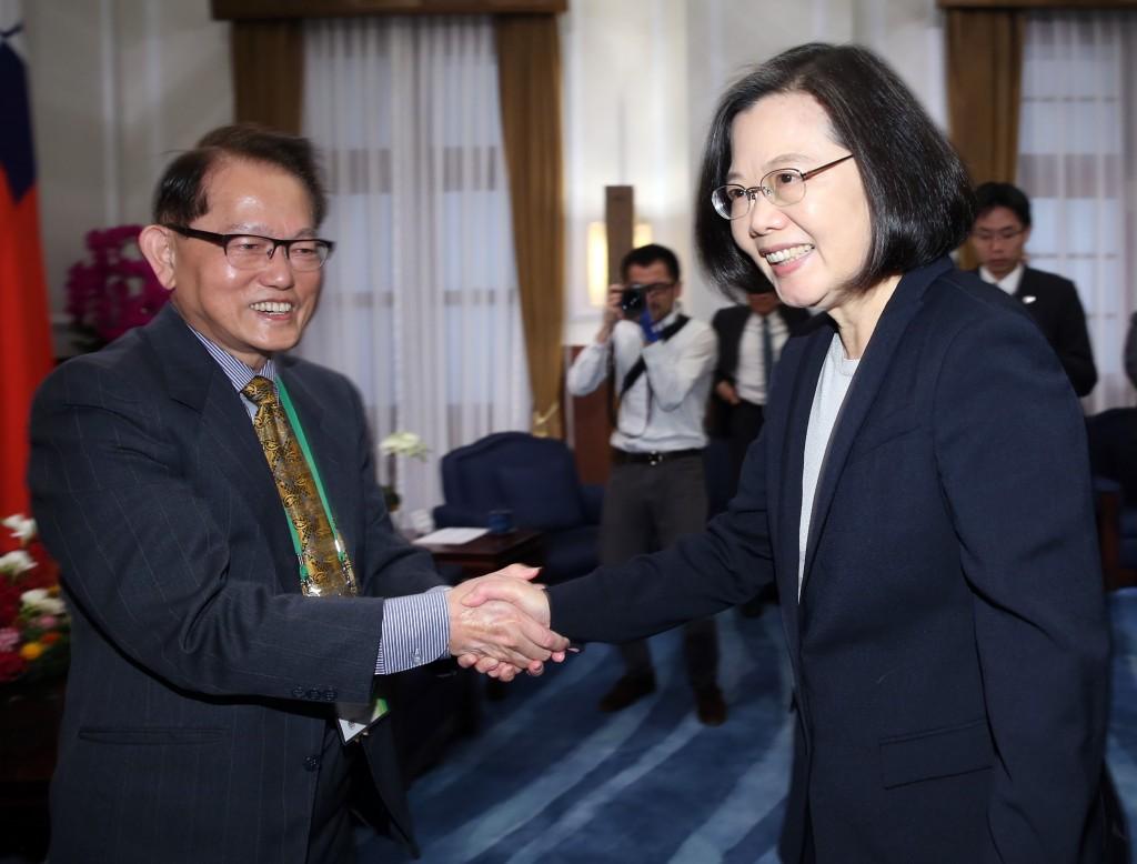 總統蔡英文(前右)27日在總統府接見「2019年海外二二八遺屬返鄉團」,與團長王克雄(前左)握手致意。
