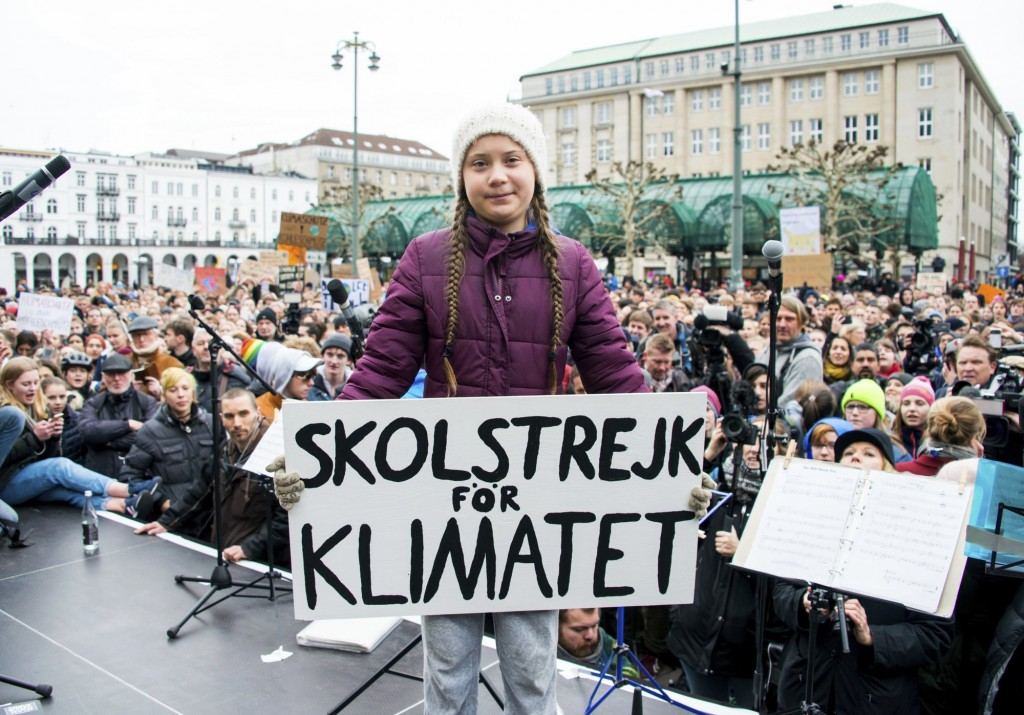 Greta Thunberg at a climate event holding up the text 'School Strike for the Climate' in Swedish.