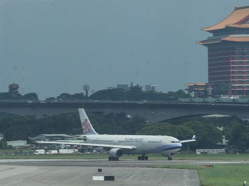 A plane on the tarmac at Taipei Songshan Airport, with the Grand Hotel in the background.